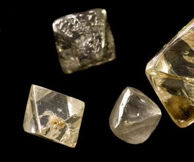rough uncut diamonds showing crystalline structure, facets and imperfections
