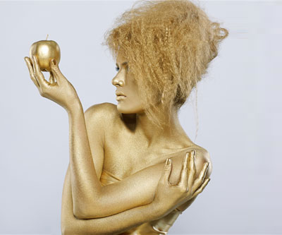 Girl with golden bodyart posing with golden apple in her hands on gray
