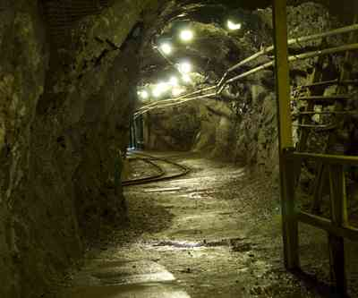 an offshoot tunnel in a copper mine with overheat steam pipes and rail lines