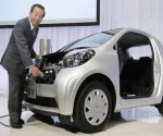 Takeshi Uchiyamada, Toyota's research chief, shows the company's upcoming all-electric city car.
