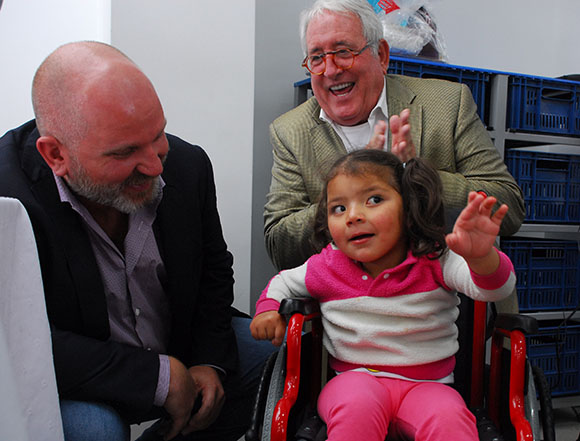Arboleda receives a wheelchair from Red Eagle CEO In Slater (left) and Gordon Holmes (right).