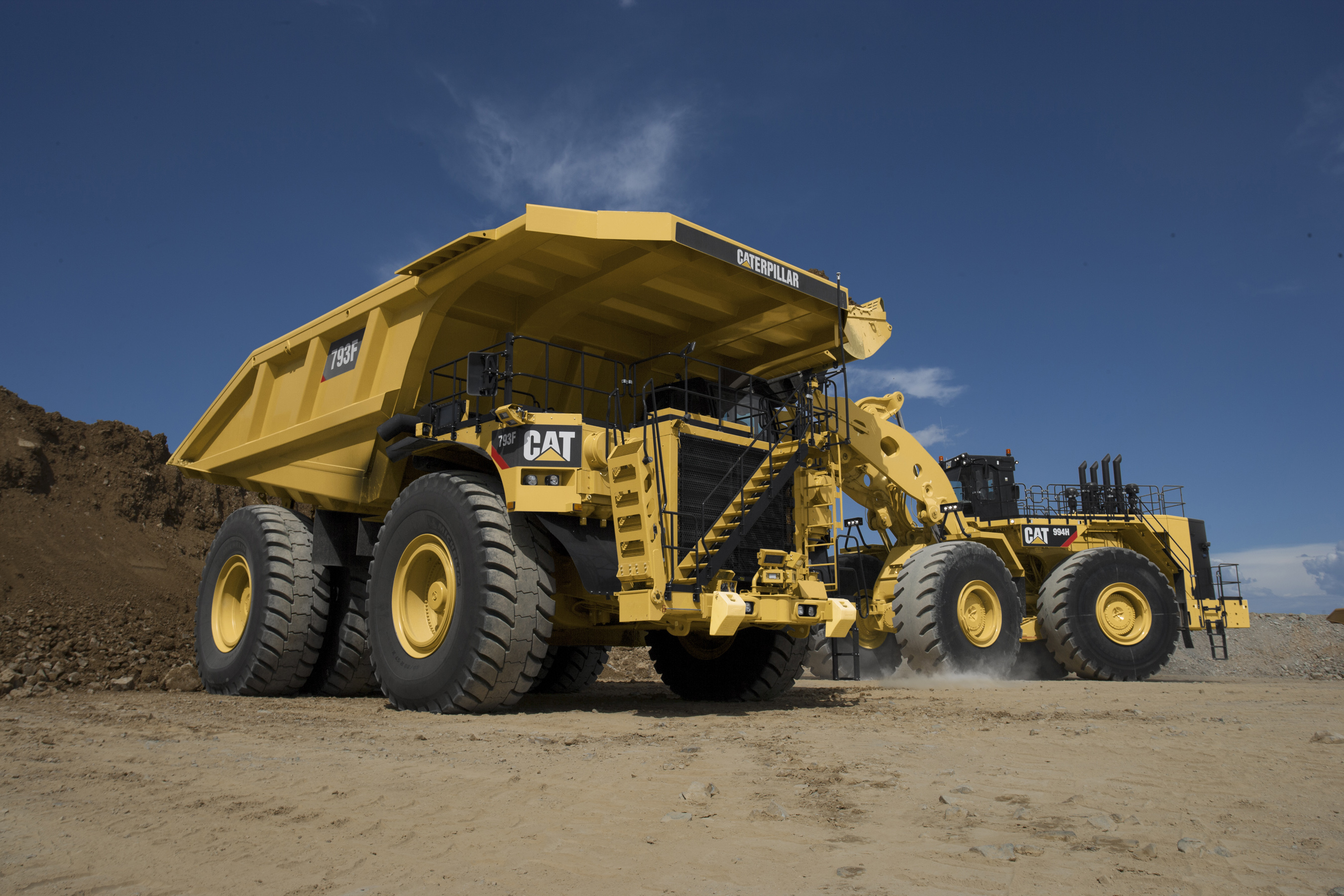 Cat 793F mining truck being loaded by Cat wheel loader.